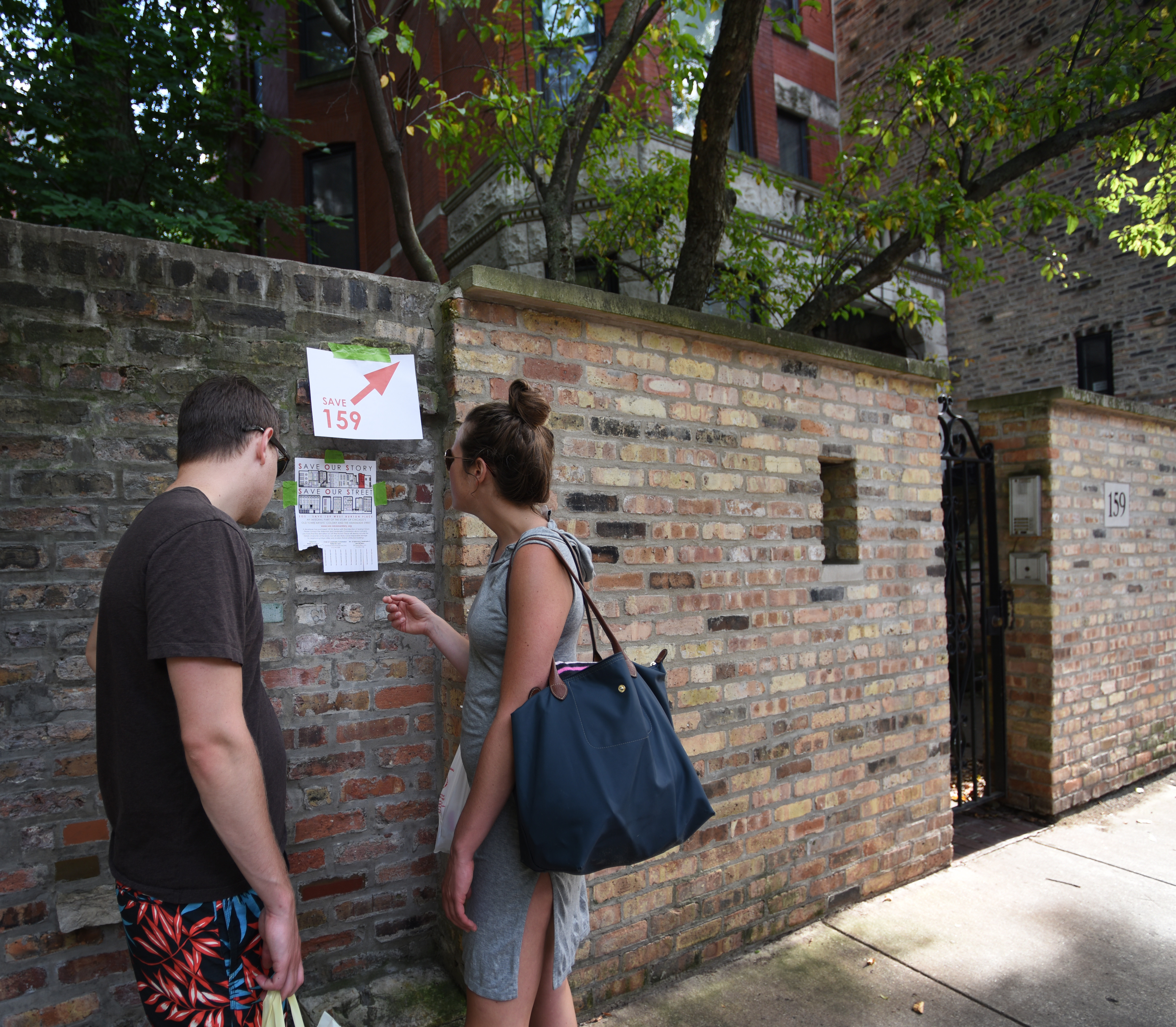 Save Our Street signs adorn wall between 155 and 159 Burton Place. Photo/Lauren Whitney