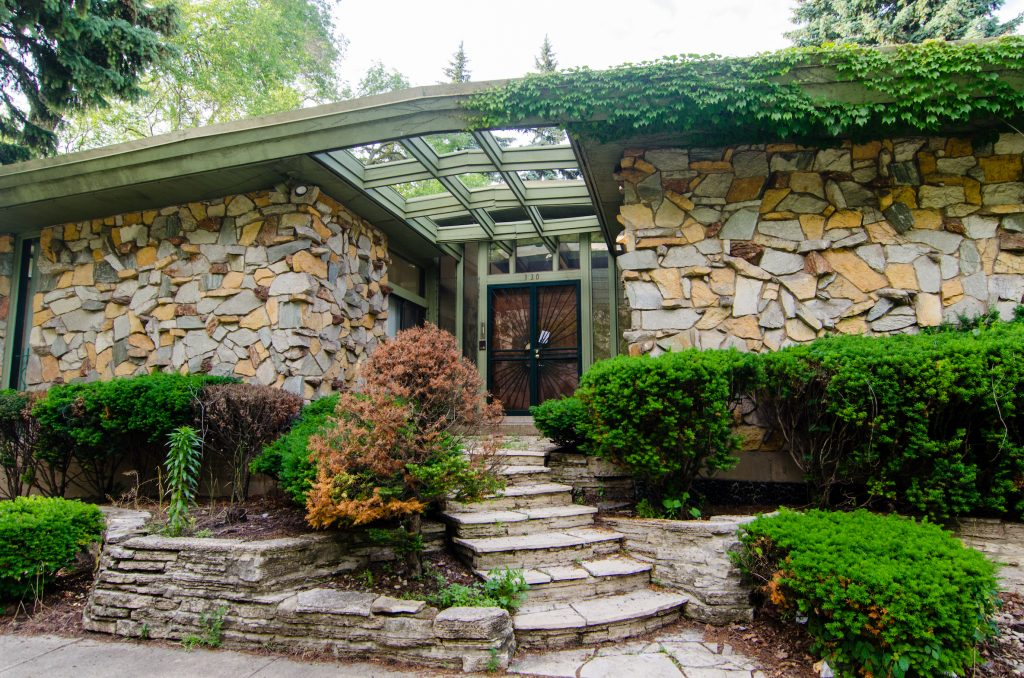Front entrance of mid-century house with ornate stone pattern facade and winding stairs