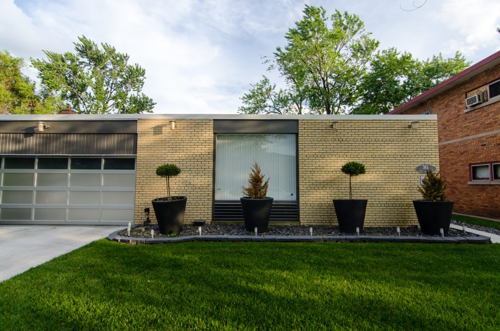 Mid-century home with beige brick, garage door, and planters spaced perfectly apart