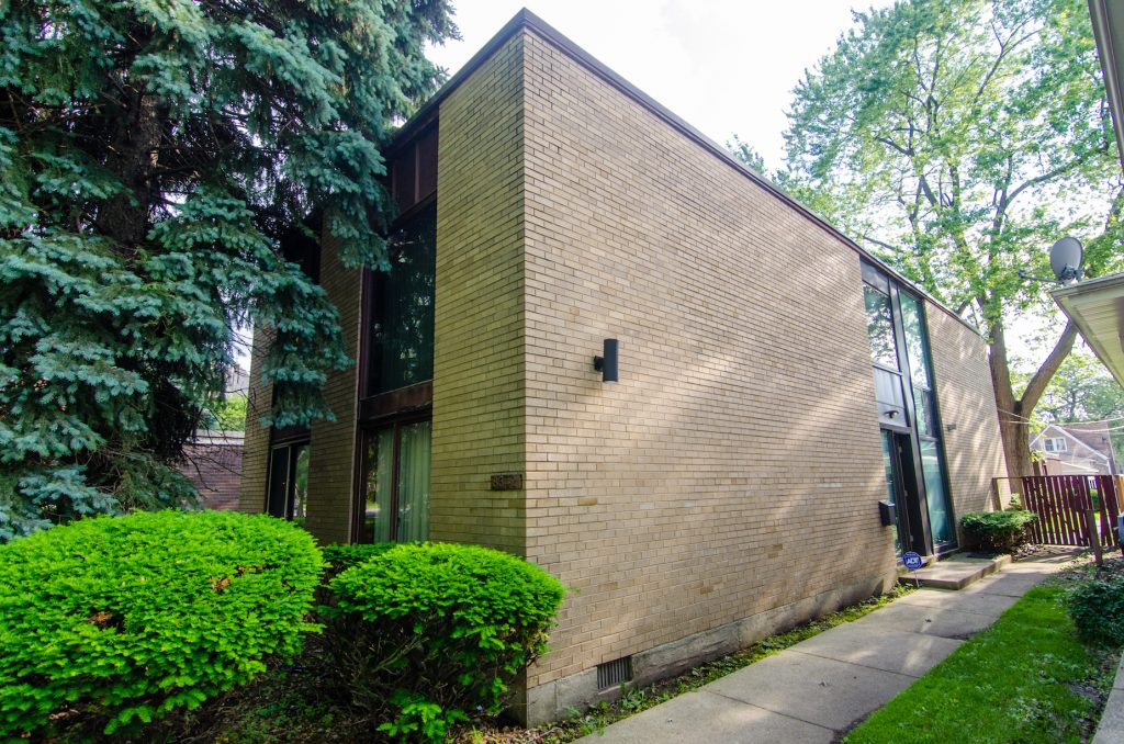Side entrance to beige brick-colored mid-century home
