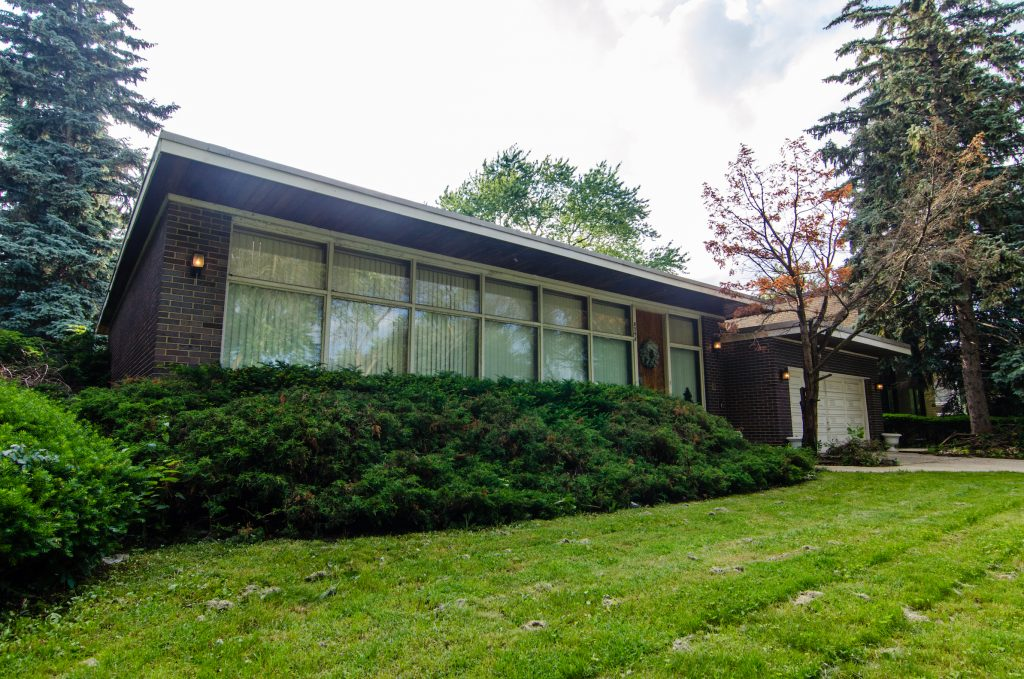 Window-covered front facade of mid-century home facing lawn