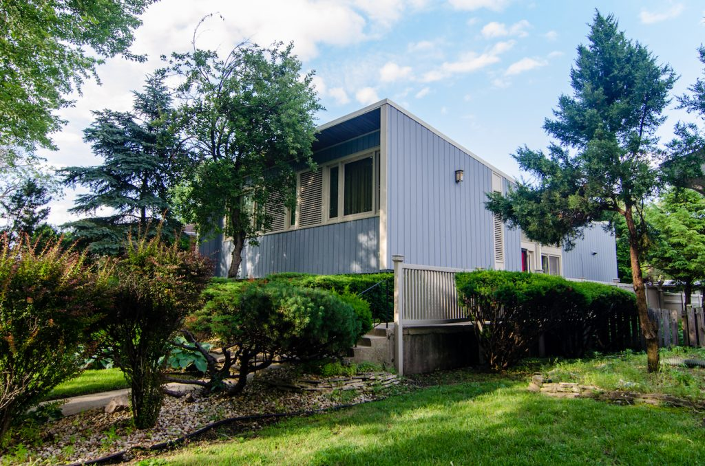 Mid-century home with blue vertical paneling surrounded by trees and lush lawn