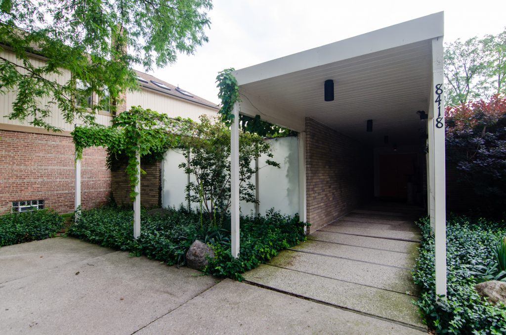 Ivy-covered walkway entrance to mid-century home