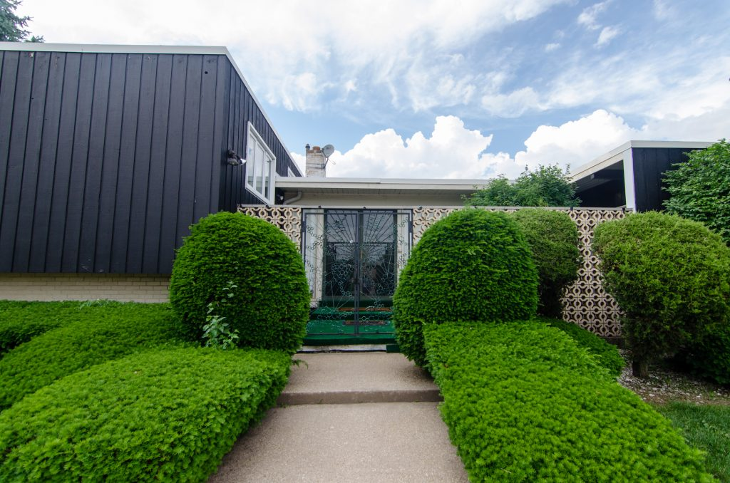 Walkway to blue mid-century home surrounded by bright green bushes leading to perforated concrete entrance