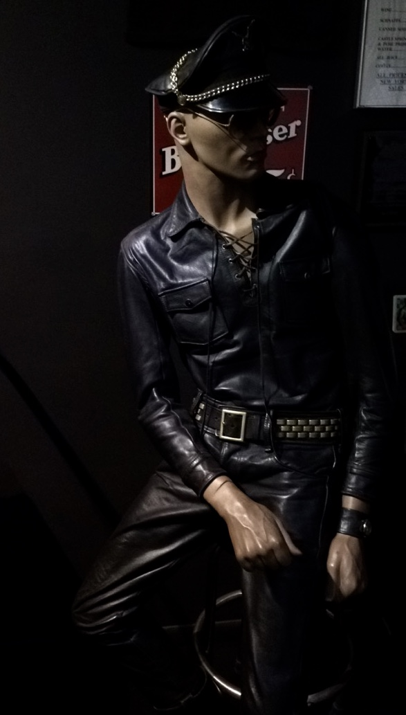 """A mannequin poses at the Museum's """"Leather Bar,"""" outfitted in a standard leather uniform."""