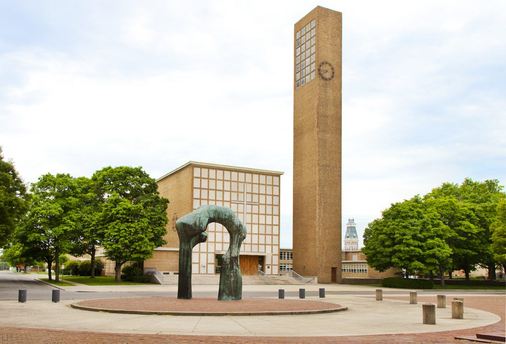 A photo of a plaza with a copper statue and a large rectangular steeple behind it.