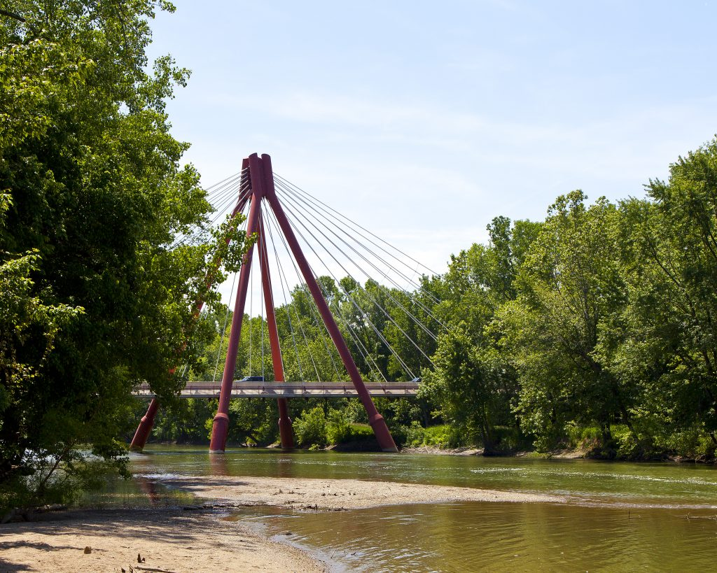 A photo of a red suspension bridge over a creek surrounded by trees.