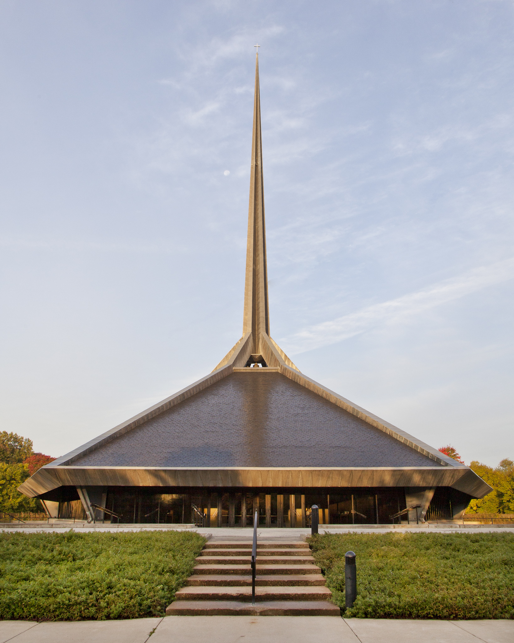 Photo of North Christian Church's triangular rooftop and sharp steeple pointing upwards towards the sky
