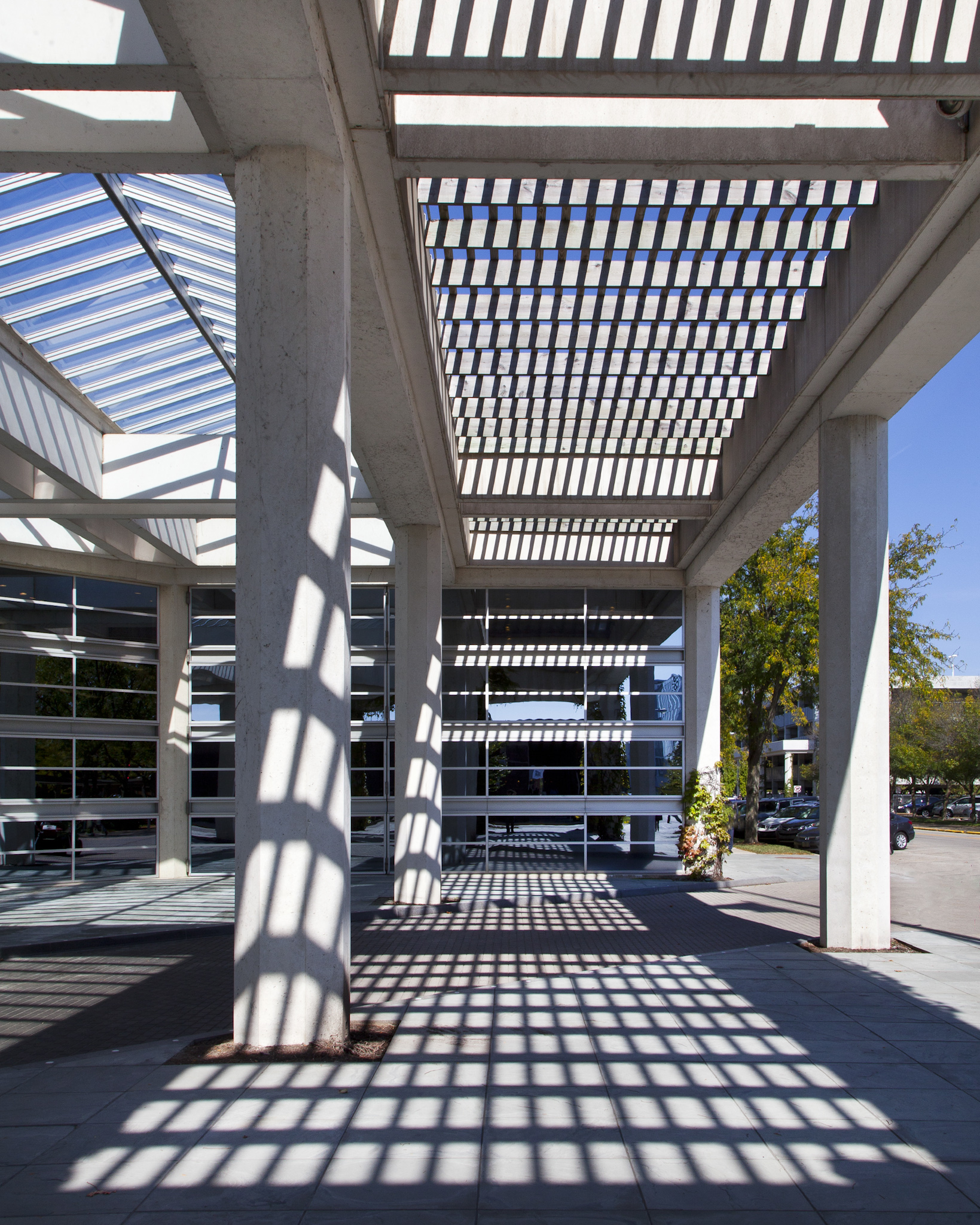 A covered walkway outside a building with sunlight coming through slits.