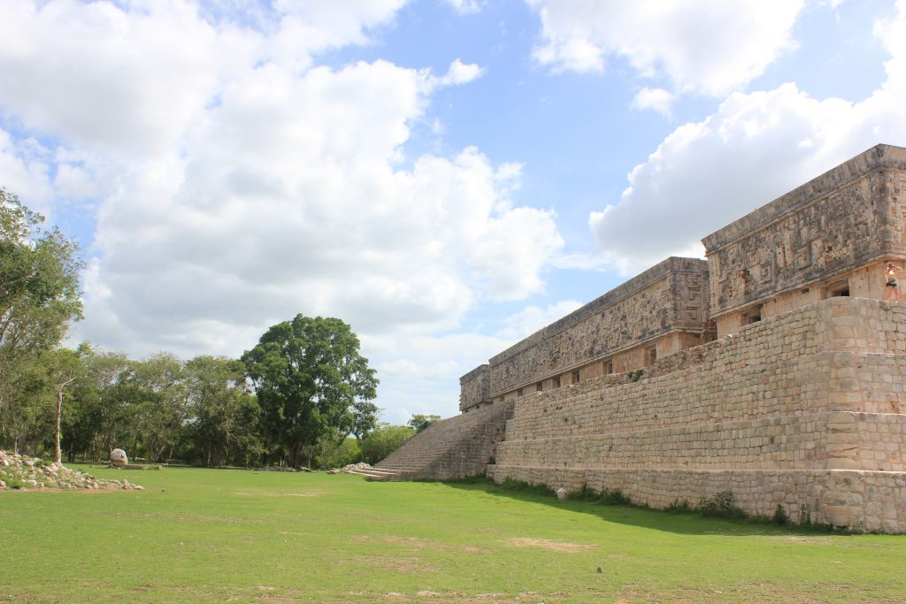 Uxmal, House of the Governor with large stone staircase and tapering walls next to open field