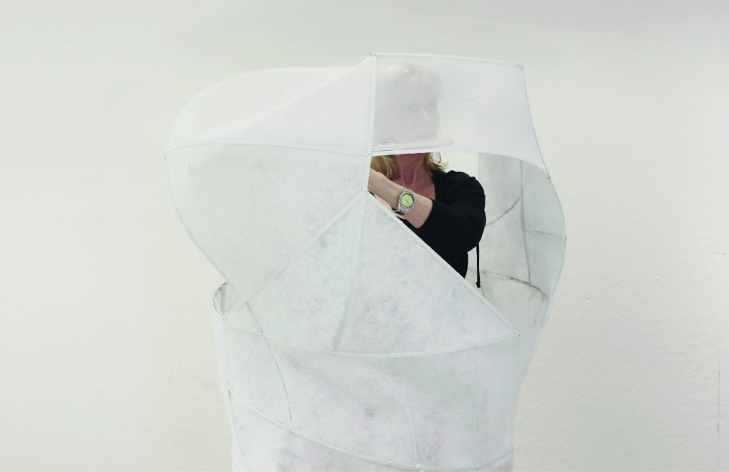 Person standing partially enclosed in white sculptural object