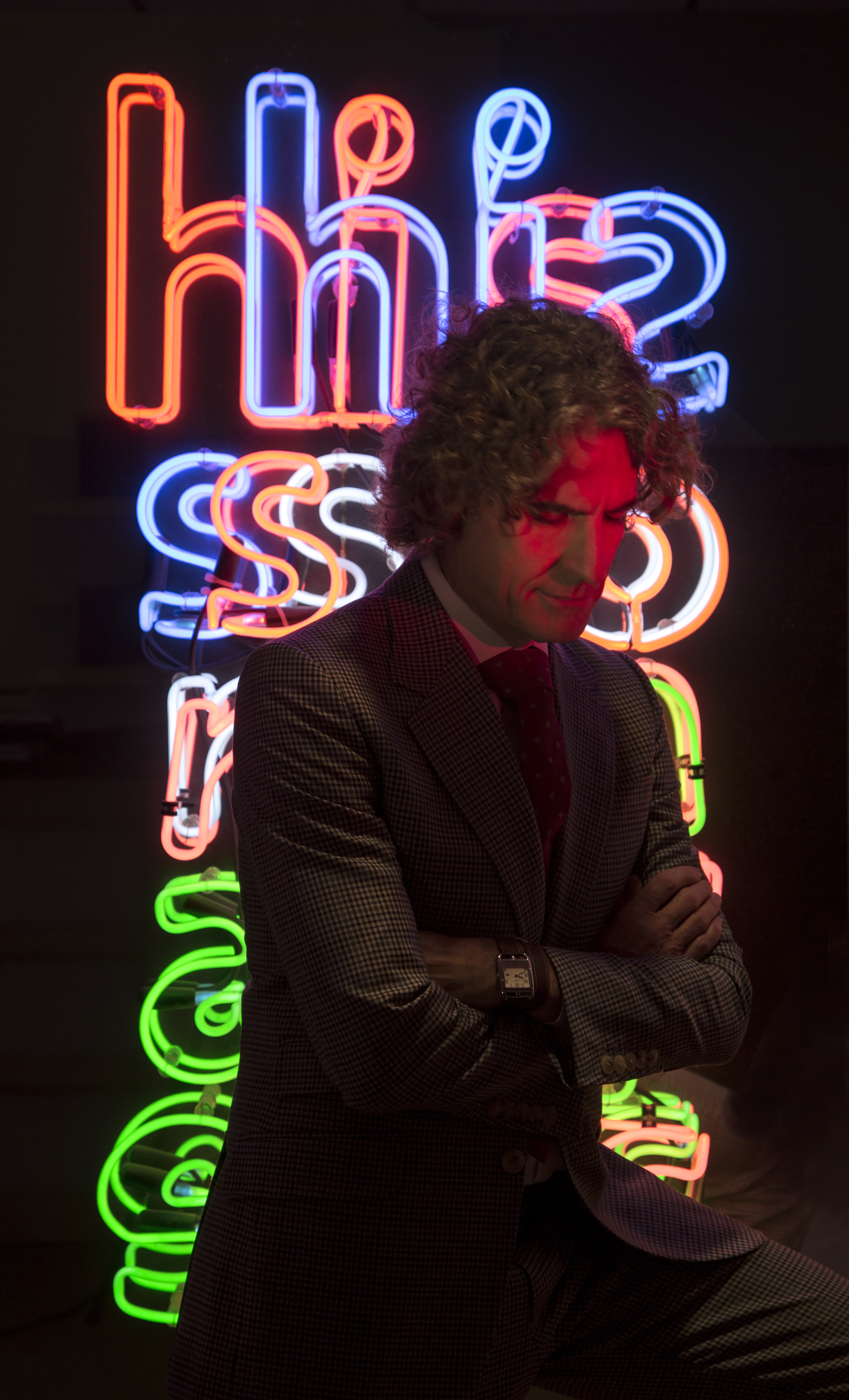 Richard Wright sitting in front of a multi-colored neon light installation.