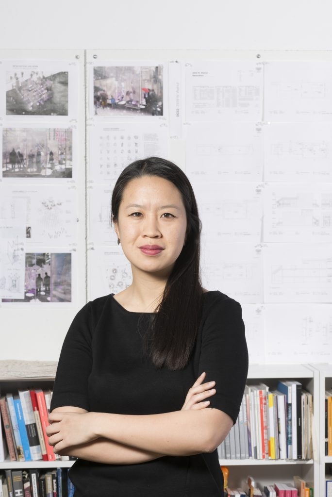 Photo of Ann Lui standing with arms crossed in front of bookshelf and photos on the wall.