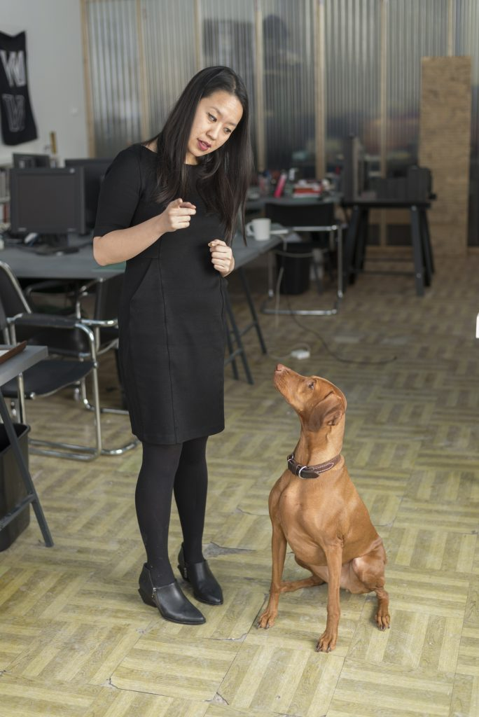 Ann Lui looking down at her dog and pointing toward the camera.