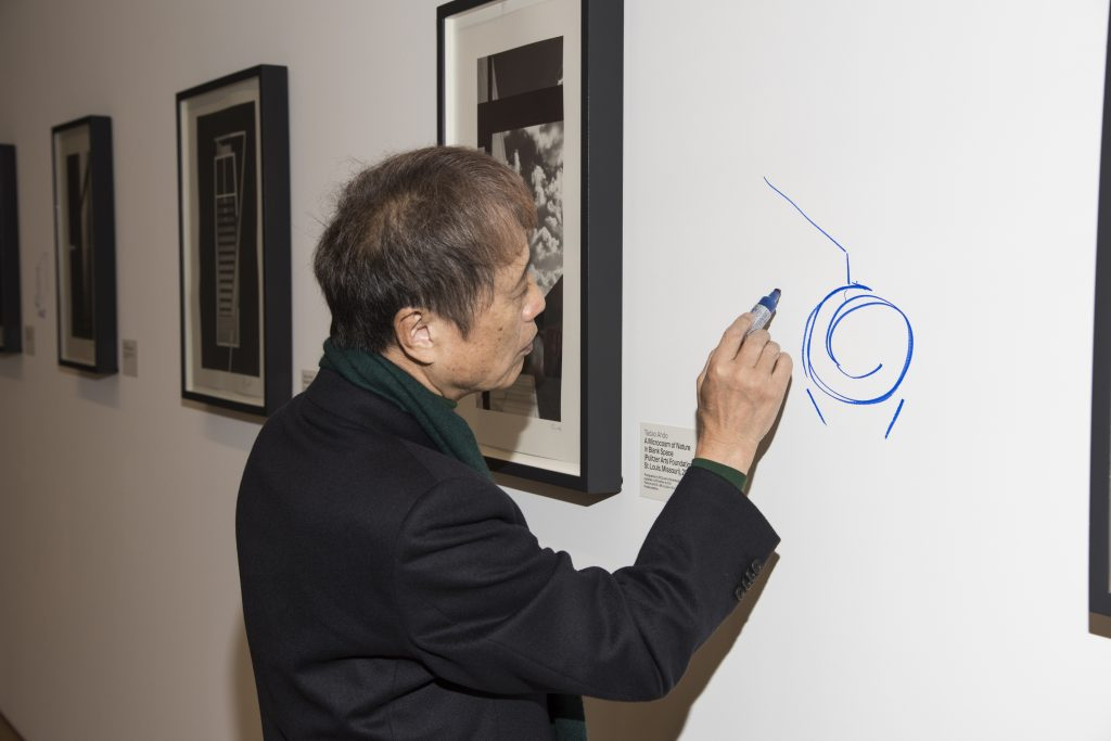 Tadao Ando drawing a diagram in blue Sharpie on an empty wall space at an exhibition of his work