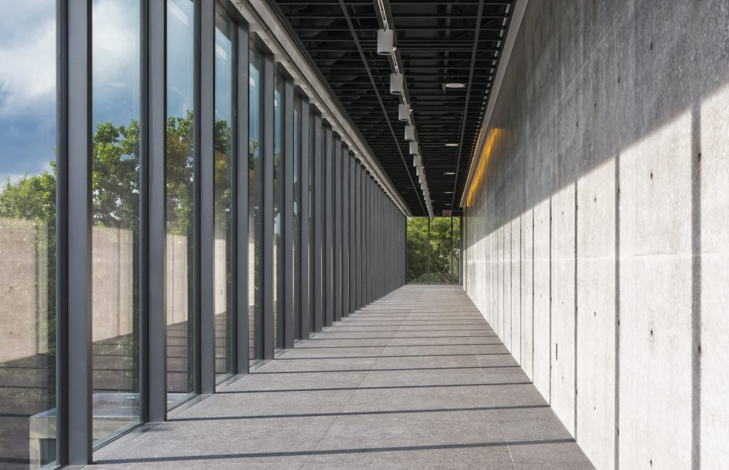 Hallway lined with floor-to-ceiling windows with sun shining and concrete wall