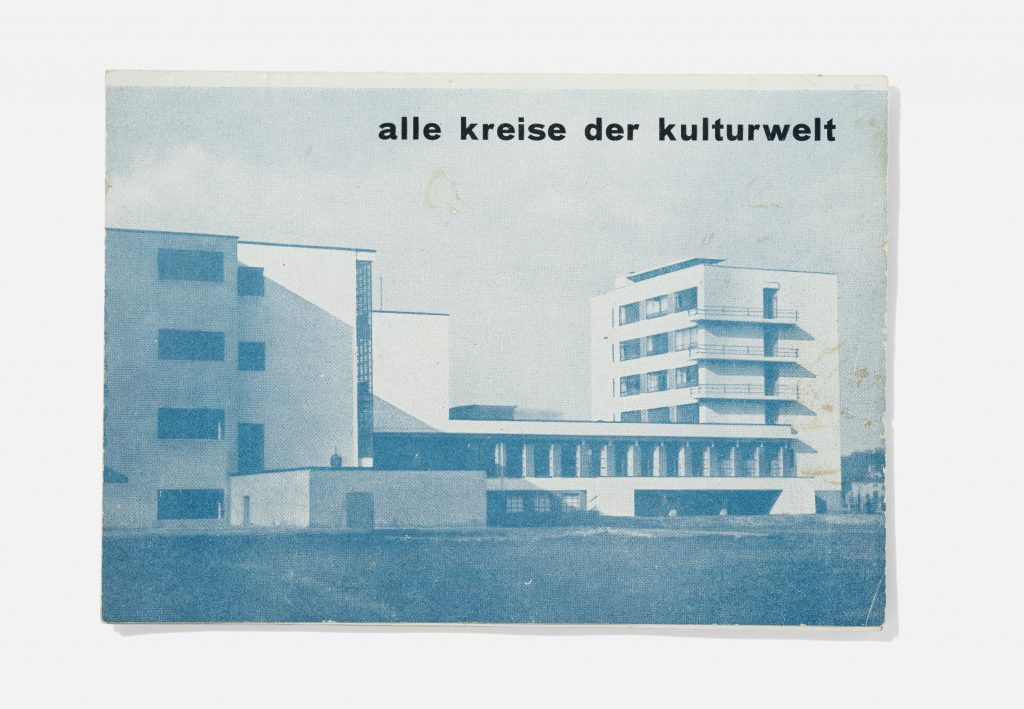 """Blue-tinted black-and-white image of four-story building with words """"alle kreise der kulturwelt"""" written above"""