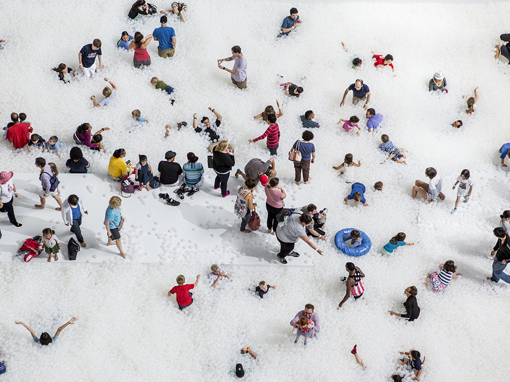 Groups of people and families playing in white ball pit and taking photos