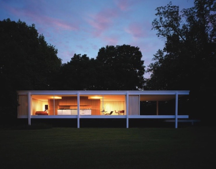 Lights from within Farnsworth House illuminate home in middle of trees at dusk.
