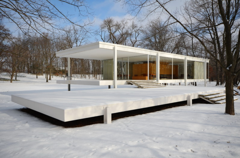 Farnsworth House surrounded by barren winter trees and snow on ground.