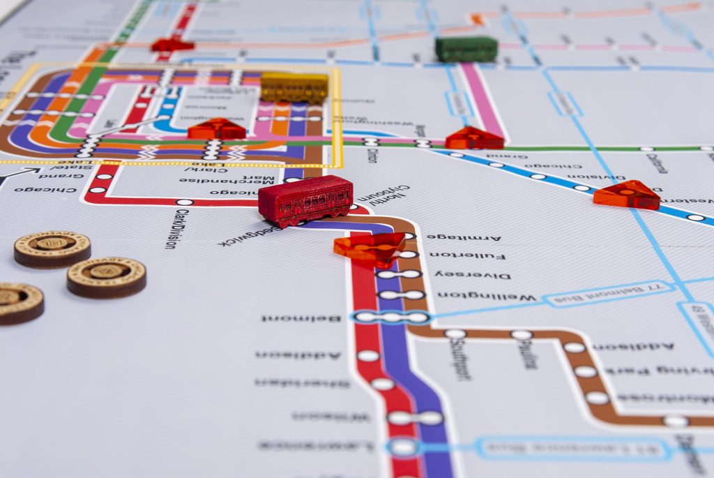 Board game map of CTA El system with train pieces and tokens.