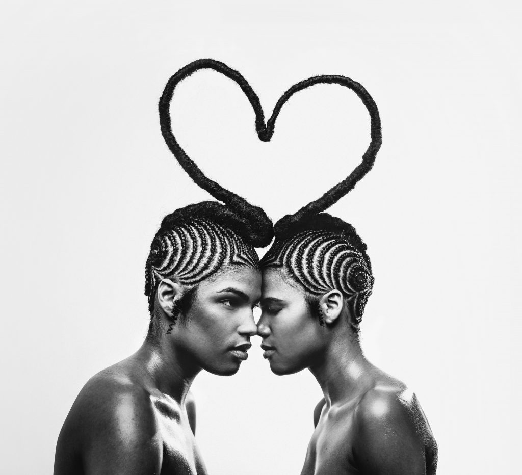 Two people facing one another connected by braid forming heart shape above their heads.