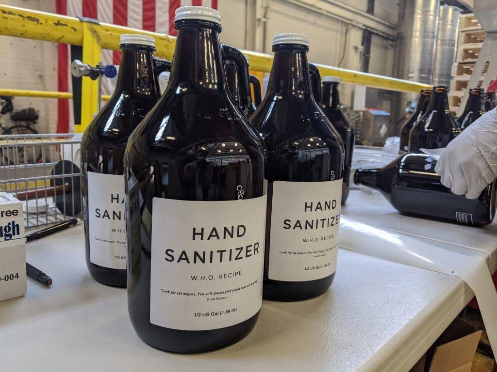 Four large bottles of KOVAL hand sanitizer