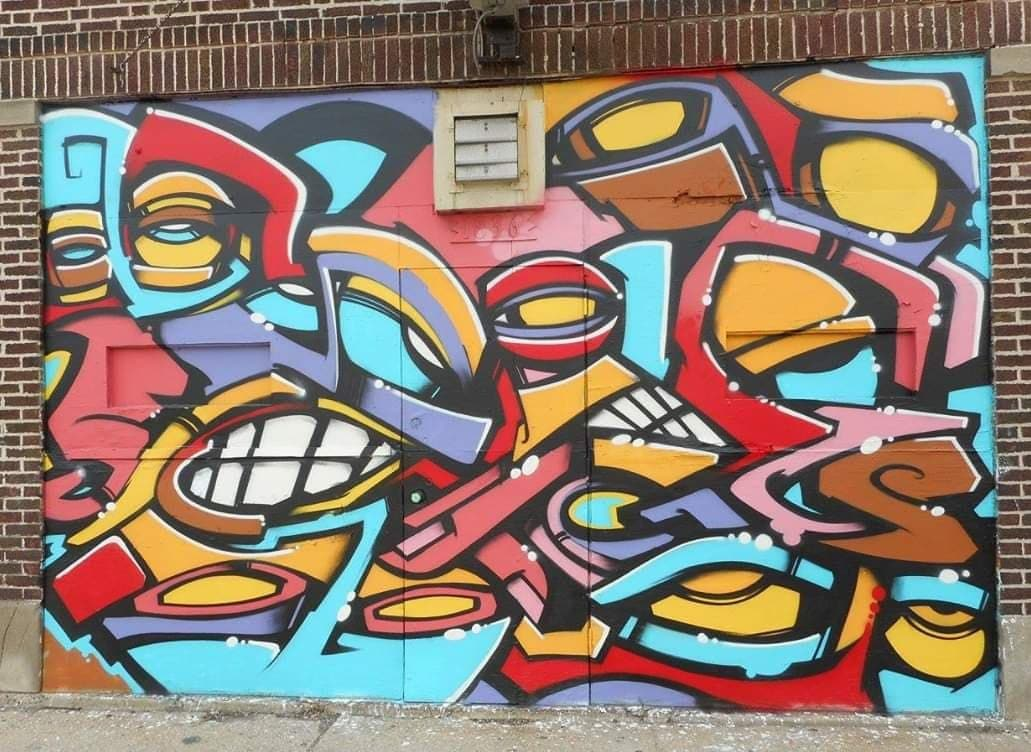 YAMS mural with teeth and eyes in jigsaw pattern inside brick frame on side of building