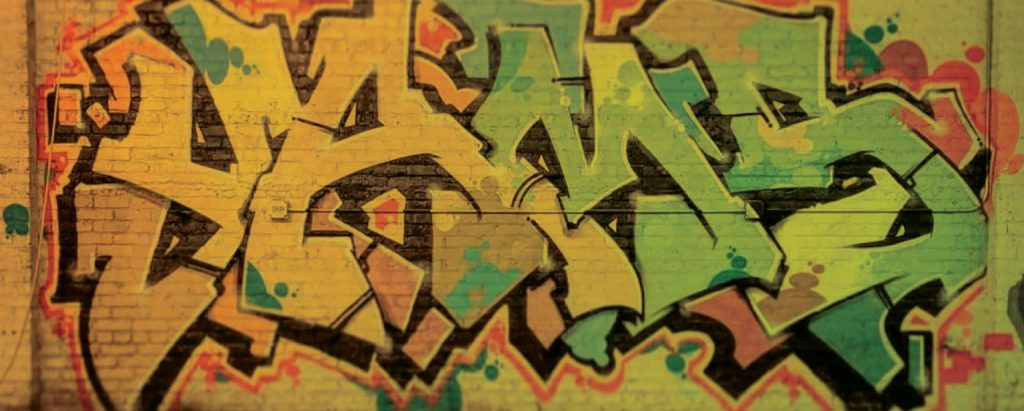 YAMS tag in green and yellow lettering on a yellow brick wall